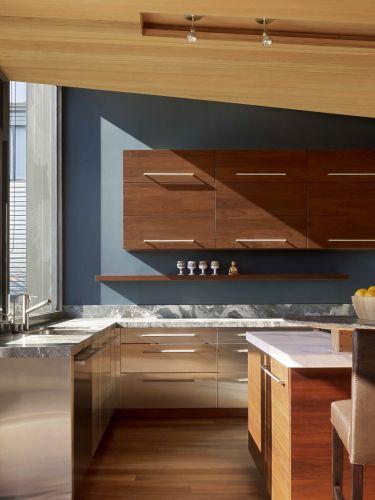 Móveis de nogueira, equipamentos de aço inoxidável e um balcão com clássico tampo de mármore compõem a cozinha da casa reconstruída por Gerry Agosta e Lisa Moresco, em San Francisco, Califórnia