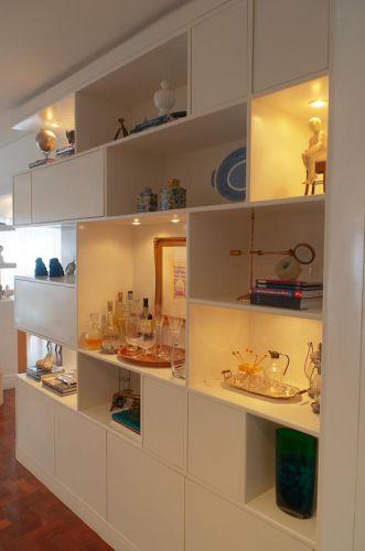 Além de separar a cozinha do hall de entrada, a estante possui nichos para exposição de peças de arte e decoração, compondo uma galeria de objetos colecionados em viagens; os nichos fechados foram reservados para guardar copos, pratos e garrafas