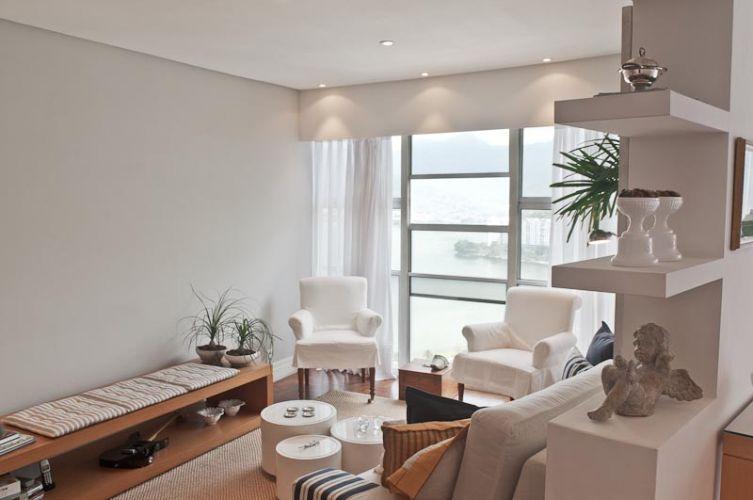 Como o pilar entre os ambientes de jantar (originalmente um dormitório) e estar não podia ser removido, foi alongado para acomodar toda a largura do sofá, além de formar uma estante