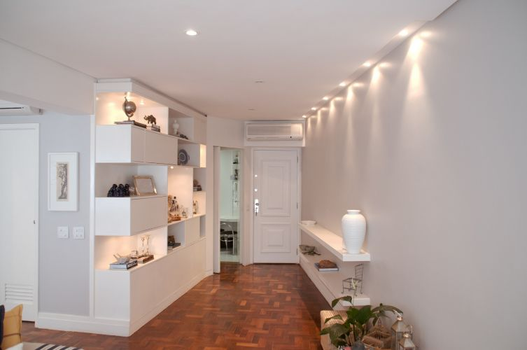 A entrada principal do apartamento abrigava originalmente uma estreita sala de jantar, que se transformou em hall e recebeu uma estante. Entre a porta de entrada e a estante, o acesso à cozinha (aberto)