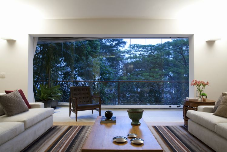 Na área de estar, poltrona Edda de couro da Catallogo compõe com os sofás e a mesa de centro. Arandelas, do Laboratório da Luz