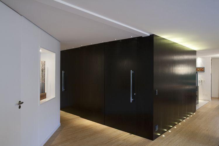 O volume de MDF revestido com lâmina de madeira ebanizada dá forma a porta de correr que separa o estar da cozinha