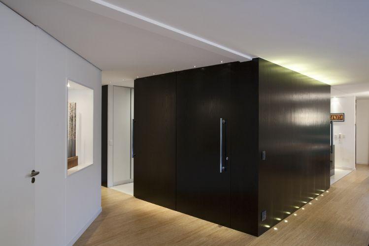 O volume de MDF revestido com lâmina de madeira ebanizada dá forma as portas de correr que isolam a cozinha
