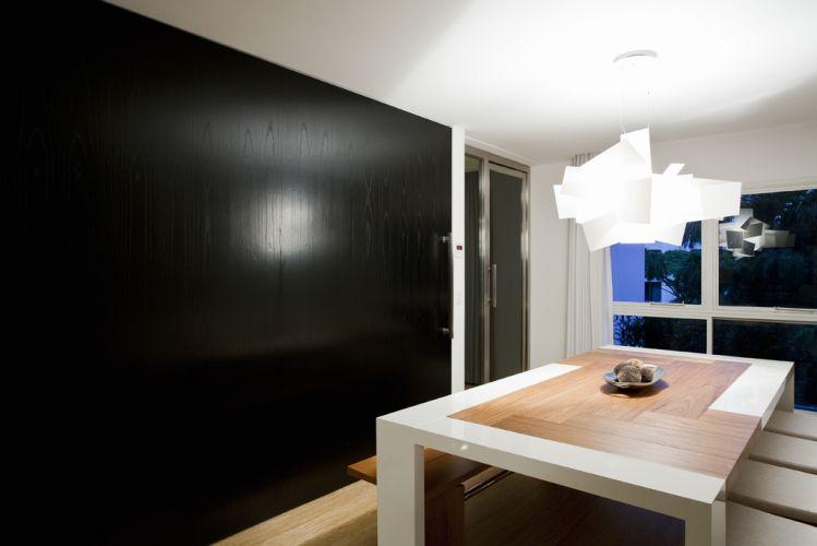 Em laca e madeira, a mesa de jantar da Clami Design compõe com o pendente Big Bang da Lumini