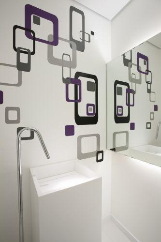 No lavabo, cuba esculpida em Corian Studio Vitty e misturador Metalbagno, piso de porcelanato simplesmente branco da Portobello. O espelho da Vidraçaria Polividros recebeu iluminação traseira. Na parede, grafismo adesivado