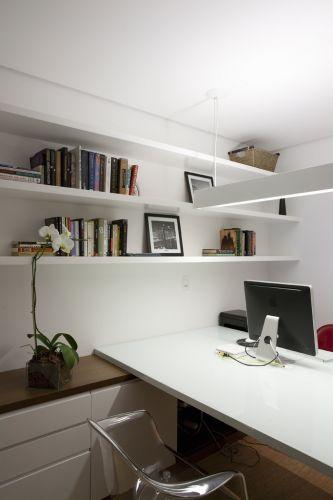 A bancada do escritório apoia-se no armário de madeira e laca, liberando o vão embaixo para maior conforto dos usuários