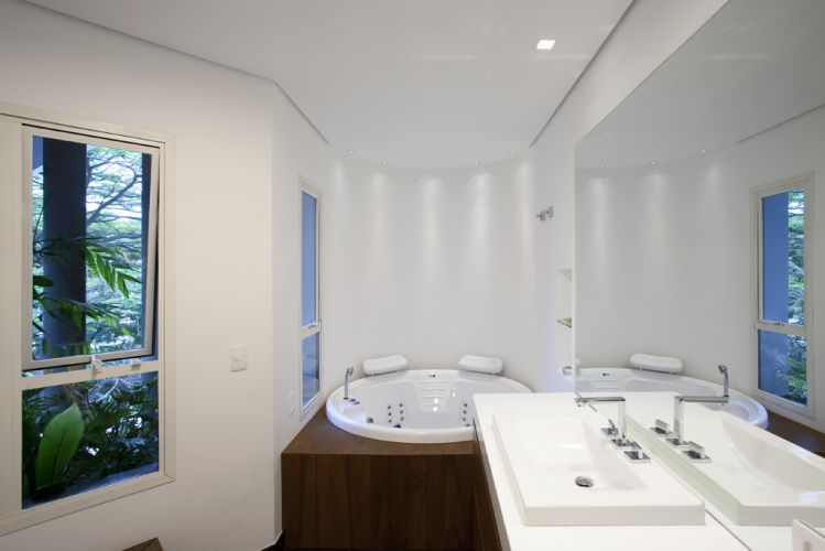 No banheiro do casal, o grande espelho sobre a bancada em Marmoglass, da Tamboré Mármores, amplia o ambiente e reflete a paisagem externa. Hidromassagem da Pretty Jet, e metais Deca