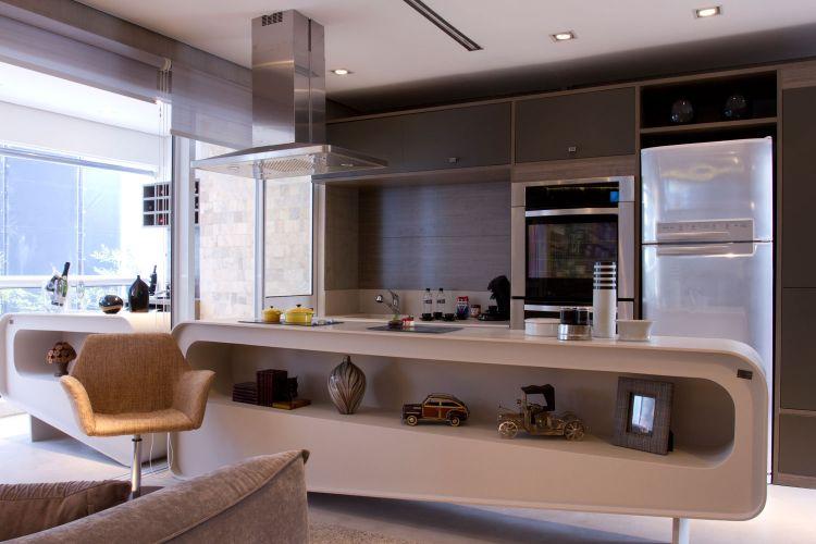 Ao fundo, a cozinha da Todeschini em padrão amadeirado acopla os eletrodomésticos e a pia e reserva espaço para as utilidades domésticas