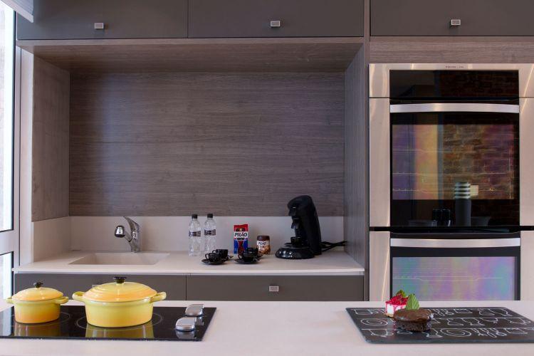 Ao mesmo tempo que separa as área social e cozinha, o balcão também abriga o cooktop e ainda pode ser usado para a manipulação dos alimentos
