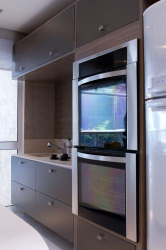 O armário planejado prevê gavetões para panelas e utensílios, além de nichos para os eletrodomésticos e espaço para a pia com tampo de corian