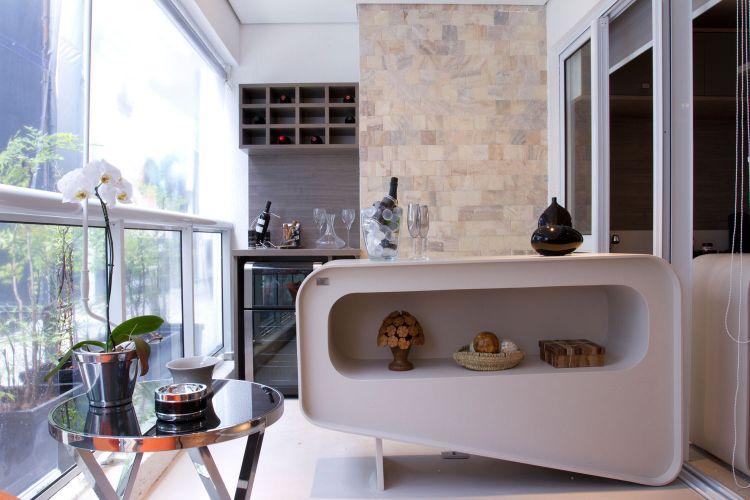 Com desenho da arquiteta Ana Bartira Brancante, o móvel feito de corian serve como bancada do bar que fica na varanda. Ao fundo, o projeto aproveitou o nicho para instalar uma adega