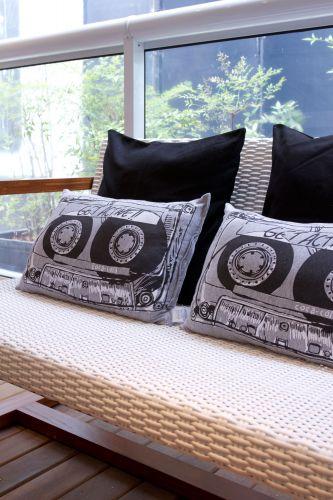 Para a varanda, a arquiteta escolheu peças mais casuais como o sofá de madeira e com assento telado. As almofadas são da Cecília Dale