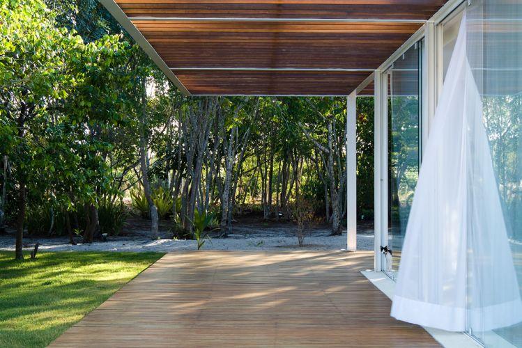Vista do salão de estar e jantar a partir da varanda. Cortinas brancas de voil garantem a privacidade suficiente à casa