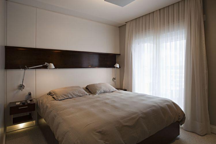 Na suíte principal, a cabeceira da cama é um painel de madeira com acabamento em laca branca e cortado de fora a fora por um nicho de imbuia. As luminárias são da La Lamp e a cortina da Ideia Básica. Detalhe para a luz indireta instalada sob as mesinhas de cabeceira