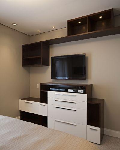 Na suíte principal, a estante mescla imbuia e laca branca, na mesma proposta da cabeceira da cama. A iluminação embutida nos nichos vai destacar os objetos expostos. O forro de gesso também embute spots de luz