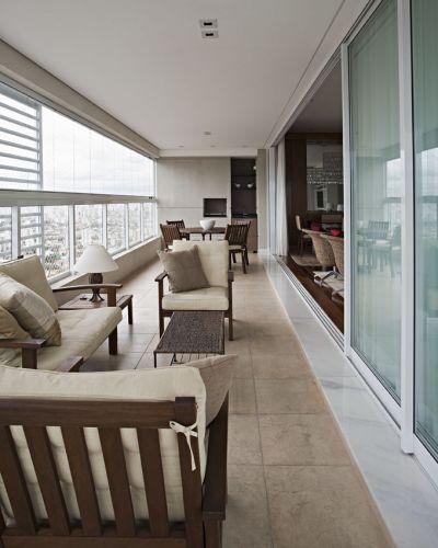 Vista da varanda com, em primeiro plano, uma sala de estar ambientada com móveis da Tok&Stok, abajur da Lustreco e almofadas da Empório Beraldin. Ao fundo, a área da churrasqueira. O piso é de porcelanato de efeito rústico