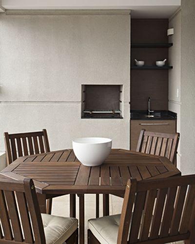 Na área da churrasqueira, o nicho da pia foi revestido com laminado melamínico amadeirado e preto. O conjunto de mesa e cadeiras é da Tok&Stok