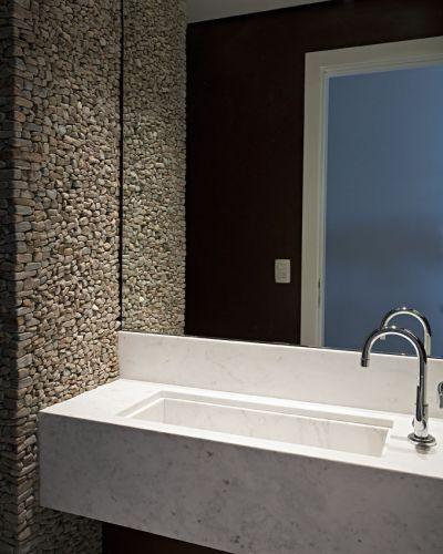 A parede revestida de seixos de pedra-madeira é o destaque do lavabo, onde a cuba da pia foi cortada na própria peça de mármore que compõe a bancada. A parede refletida no espelho foi pintada com tinta bordô, tonalidade exclusiva da Suvinil
