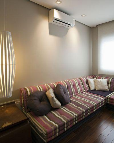 Sala íntima com futon e almofadas da Futon e Cia. A luminária pendente é da Lustreco e a cortina de enrolar em tela solar é da TPS