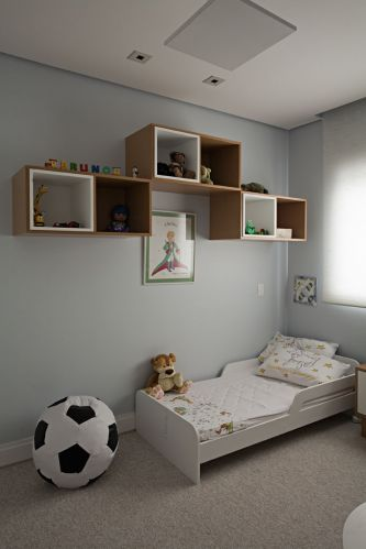 No quarto do menino, sobre a mini-cama da Tok&Stok foram colocados seis nichos produzidos pela marcenaria Detalhe e Entalhe com freij natural e com acabamento de laca branca. A cortina de enrolar  da TPS. No piso foi colocado carpete da Carpet Express
