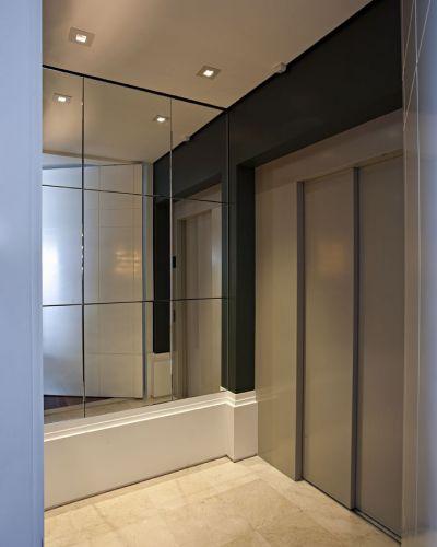No hall do elevador, o rodapé largo, a parede com lâminas retangulares de espelhos e a outra, com pintura verde escuro, conferem um acabamento sofisticado, enfatizado pela iluminação