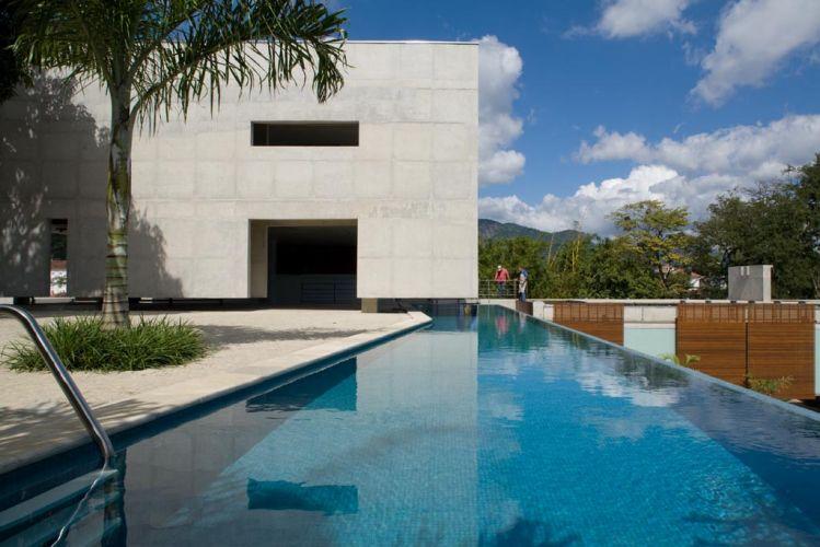 A piscina, instalada no platô de concreto mais elevado, possui interligação com o bloco do estar