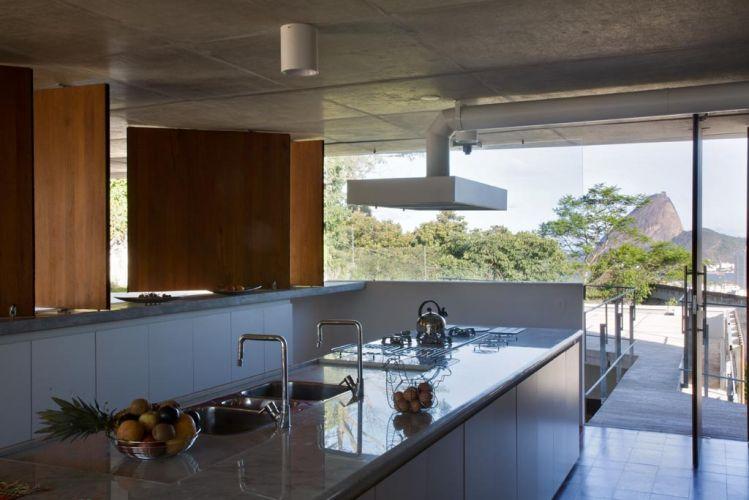 A cozinha, toda branca, tem a inspiradora paisagem do Pão de Açúcar. Painéis pivotantes de madeira controlam insolação e ventilação