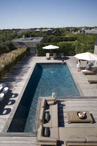 A mesma espécie de madeira, o cedro, foi empregada na construção do deck da piscina, obtendo uma uniformidade de cor com o terraço, e a fachada da casa. No perímetro do terraço, o guarda-corpo transparente permite a continuidade entre o azul da água da piscina e do mar