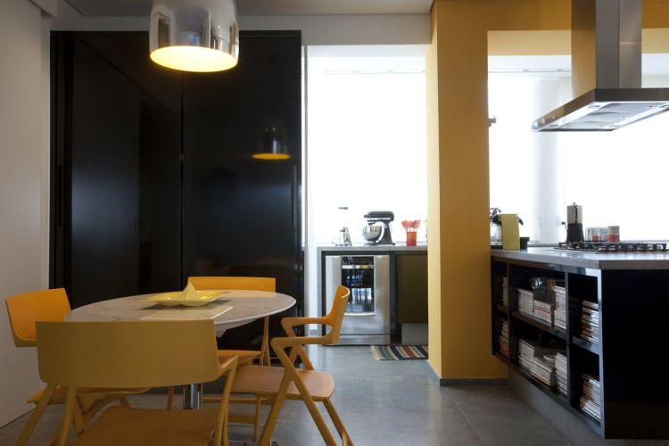 Para criar a cozinha gourmet, o projeto eliminou paredes e integrou a rouparia e o lavabo ao ambiente. A viga e o pilar, destacados com a cor laranja, e a ilha executada pela Marcenaria Madeirart dividem a área em setores de preparo e de refeição