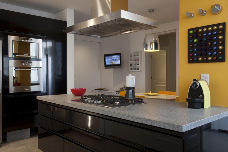 A ilha de MDF e laminado brilhante acopla o cooktop e guarda os utensílios. A coifa de aço inox contrasta com o tampo de granito e purifica o ar ambiente durante a cocção