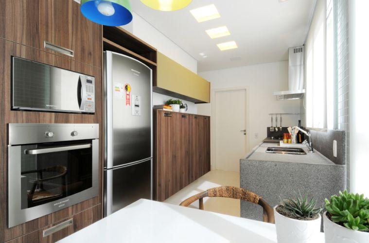 Fugindo ao trivial, a cozinha executada pela Kitchens tem mobiliário revestido por lâminas escuras. Um dos módulos dos armários (ao fundo, em cima) recebeu porta de vidro amarelado. O apartamento de 150 m² no Cambuí, em Campinas (SP), tem decoração assinada pela arquiteta Elaine Carvalho