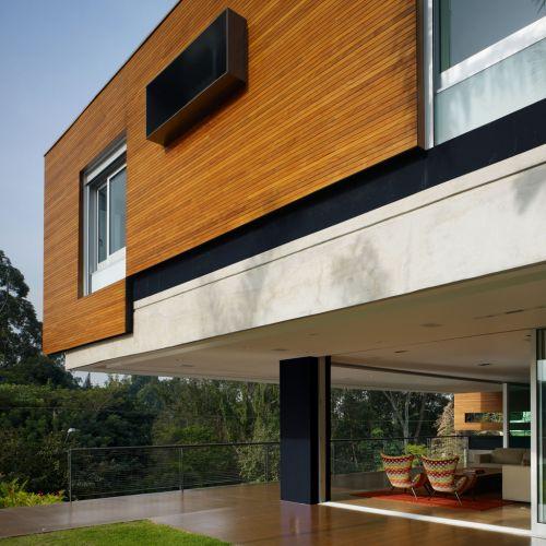 Os painéis de madeira que protegem as fachadas laterais da construção são recortados em torno das janelas. O quadro de aço contorna as janelas dos banheiros. A casa urbana e moderna tem projeto de Biselli Katchborian Arquitetos