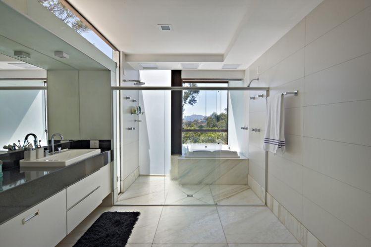 O banheiro da suíte principal, com abertura voltada para a frente do terreno, oferece vista para a serra do Curral, ao fundo (através da janela). A casa no Bosque da Ribeira, em Nova Lima (MG), é um projeto dos arquitetos Eduardo França e Letícia de Azevedo