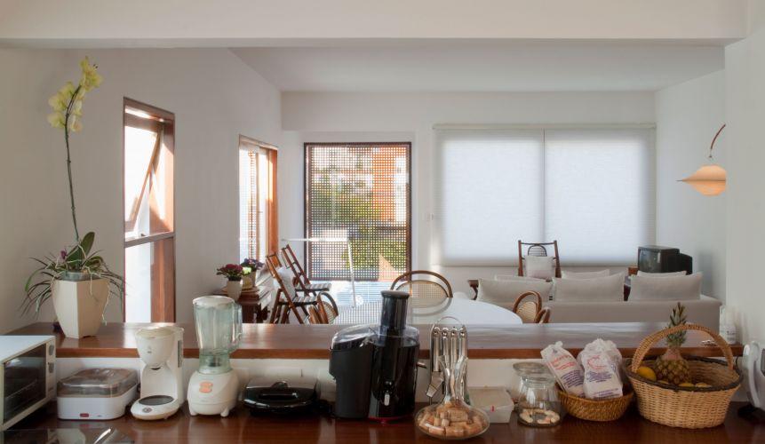 Entre a cozinha e o living, a bancada produzida pela Marcenaria Baraúna serve, de um lado, à cozinha, apoiando eletromésticos, e, do outro, à sala de jantar