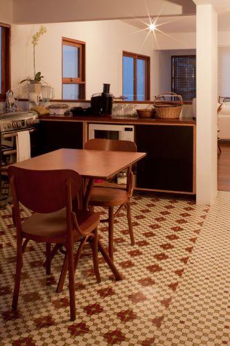 A cozinha de inspiração colonial tem espaço até para uma pequena copa, com mesa e duas cadeiras. No piso, ladrilho hidráulico da Dell Piage. Sob a bancada, o armário de compensado naval embute o microondas