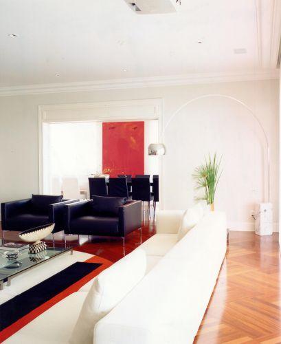 Integrado ao estar, o ambiente de jantar tem mobiliário em preto e branco. A cor vem do intenso vermelho da tela