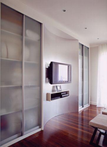 Na marcenaria do armário, um nicho em curva abriga o monitor de TV