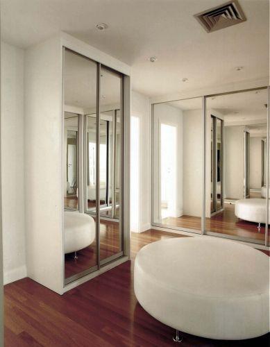 No closet, muitos armários fechados por portas espelhadas que propiciam a visão a partir de qualquer ângulo. O pufe, no centro, serve de apoio e completa a ambientação