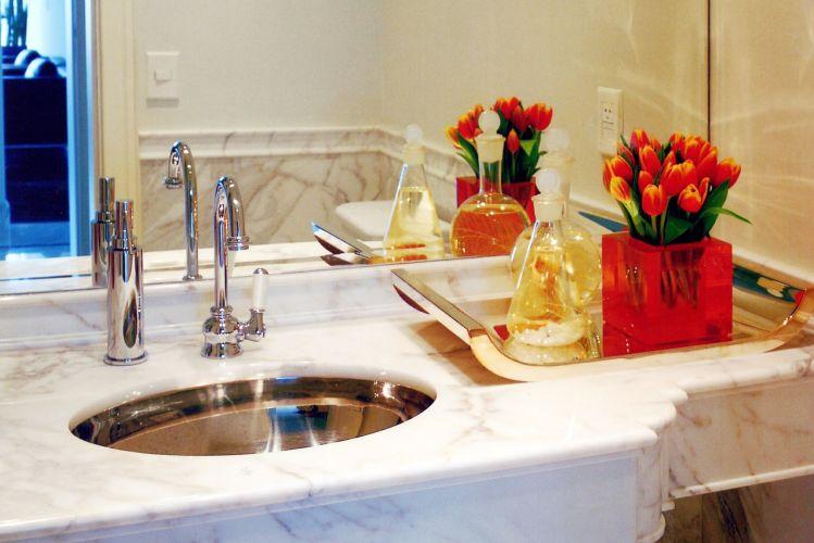 O lavabo tem design clássico com chanfro arredondado no tampo de mármore de Carrara. Os metais com linhas mais retro são da Deca