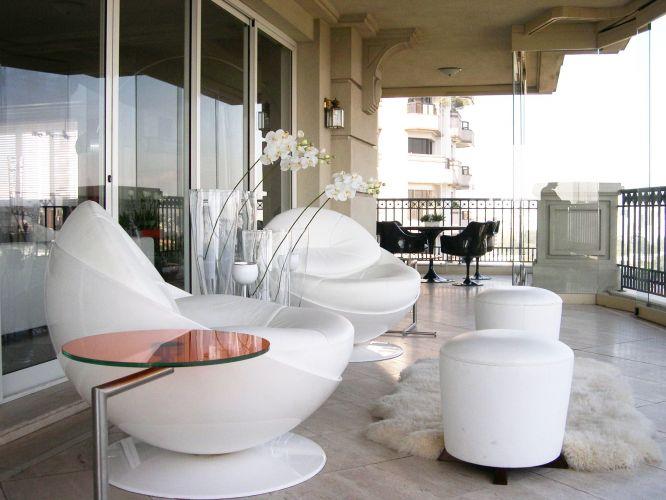 No terraço, as mesmas poltronas futuristas da Brentwood compõem áreas de estar. Ao fundo, uma mesa com cadeiras do modelo Tulipa criam um canto de refeições