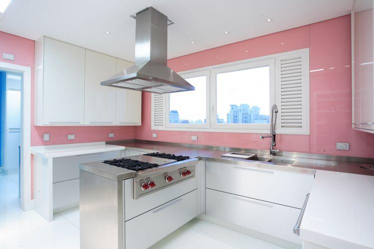 Na composição desta cozinha, a arquiteta Brunete Fraccaroli inovou ao contrastar o branco do mobiliário com acabamento de parede em vidro revestido de película rosa. Para dar maior funcionalidade e aproveitar melhor o espaço, centralizou a ilha com fogão e criou duas áreas de trabalho