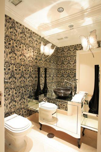 O projeto do lavabo mostra o ecletismo presente na linguagem de Brunete Fraccaroli. O revestimento floral, os vaso bojudos, a luminária em forma de borboleta e o detalhe curvilíneo do móvel espelhado conferem ao ambiente um estilo particular