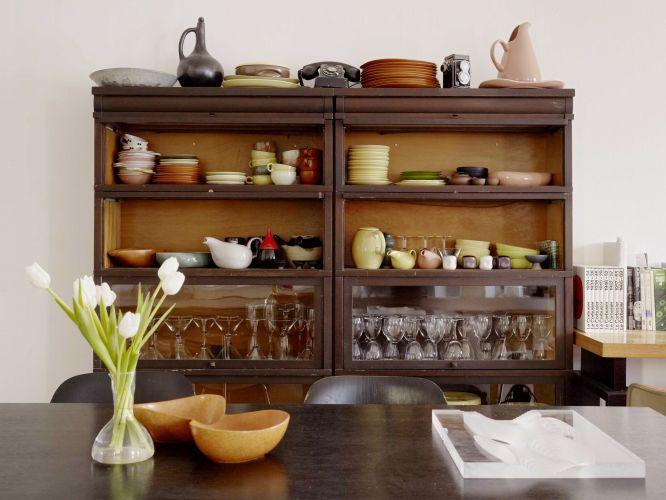 Na sala de jantar da casa de Raveevarn Choksombatchai, em São Francisco, Califórnia, a cristaleira vintage abriga as cerâmicas Russel Wright e Roseville