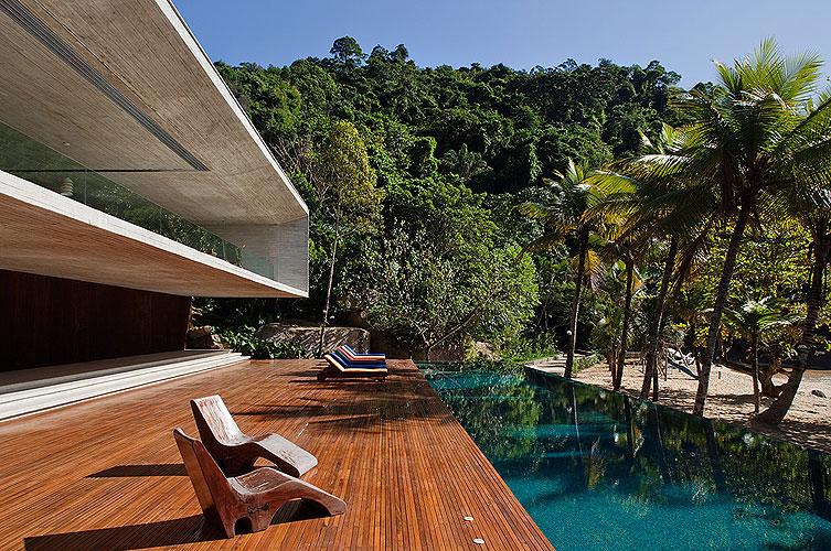 O deck, feito de ripas da madeira, estabelece uma transição entre a casa e a piscina que, apesar da ortogonalidade, parece natural junto à praia graças à sua tonalidade de azul, parecida com a cor do mar local