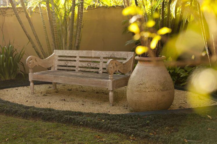 No fundo do jardim, Faisal criou um canto de contemplação, forrando o chão com pedrisco, contornado por grama preta e incluindo o banco balinês do acervo da família e o vaso cerâmico