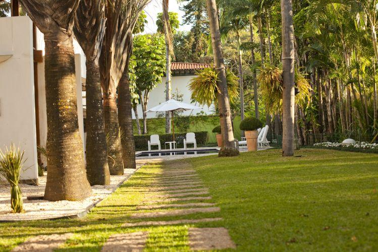 Pisadas de granito indicam o caminho da piscina. A casa é contornada por palmeiras triangulares sobre pedriscos