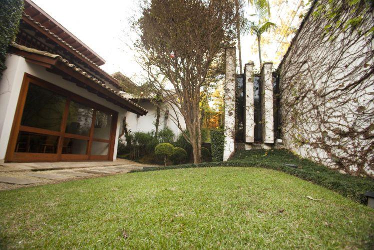 Fundo do jardim, com muro coberto por falsa vinha e chão de grama esmeralda emoldurada por grama preta