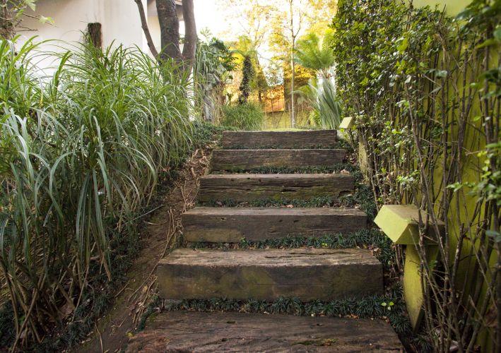 A escada de dormentes, delimitada à esquerda por mini pândanos, leva aos fundos do jardim. A murada à direita é revestida por murta