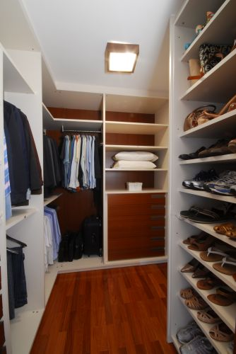 Projetado pelo escritrio Mad Campos Arquitetura, esse closet tem armrios da Ornare. Foi desenhado para um casal.  todo revestido com MDF, possui puxadores embutidos, gaveteiros e muitas prateleiras. Sem portas nos mdulos, o espao  separado do dormitrio apenas por uma porta de correr