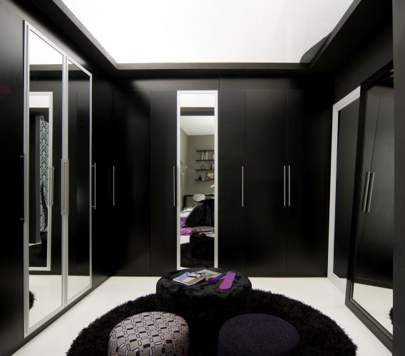 Alberto Radespiel criou esse closet para a Mostra de Quartos Lider Interiores. Os armrios possuem muitas gavetas, todas com corredias telescpicas. As portas dos armrios acabadas com laca preta fosca foram intercaladas por algumas espelhadas. No centro e sobre um tapete felpudo, o decorador colocou trs pufes revestidos de seda. A iluminao difusa vem de uma sanca no gesso fechada com acrlico branco leitoso